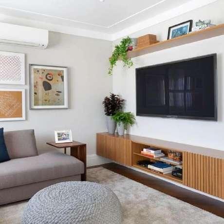 31. TV direto na parede de sala de estar com rack de madeira suspenso – Foto: Jeito de Casa