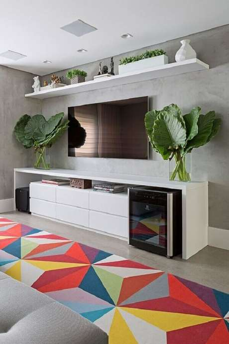 32. Sala de estar moderna decorada com tapete geométrico colorido e TV direto na parede de cimento queimado – Foto: Casa de Valentina