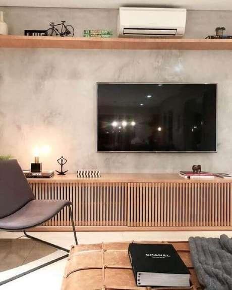 33. TV direto na parede de cimento queimado de sala moderna com rack de madeira – Foto: Archilovers