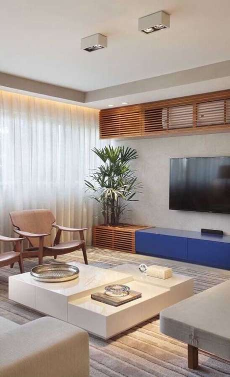 34. Decoração moderna para sala com TV na parede e rack planeada azul – Foto: Apartment Therapy