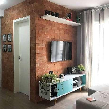 36. TV direto na parede de tijolinho de sala pequena com rack retrô – Foto: Pinterest
