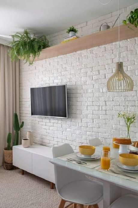 37. TV direto na parede de sala branca com rack retrô e vasos de plantas – Foto: Pinterest
