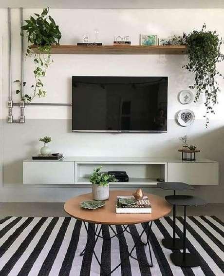43. TV direto na parede de sala cinza e branca decorada com tapete listrado e mesa de centro redonda – Foto: Apartament Therapy