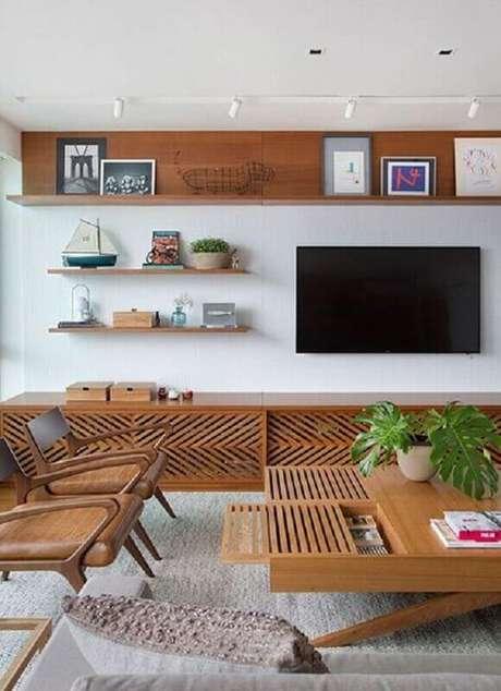 44. Decoração de sala planejada com móveis de madeira e TV na parede sem painel – Foto: Behance
