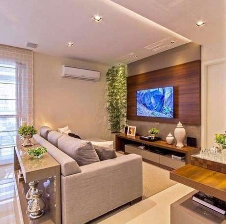 45. Sala de estar decorada com sofá cinza e suporte para TV na parede – Foto: Pinterest