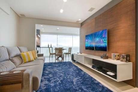 46. Painel de madeira como suporte para TV na parede de sala decorada com sofá cinza e tapete azul – Foto: Pinterest