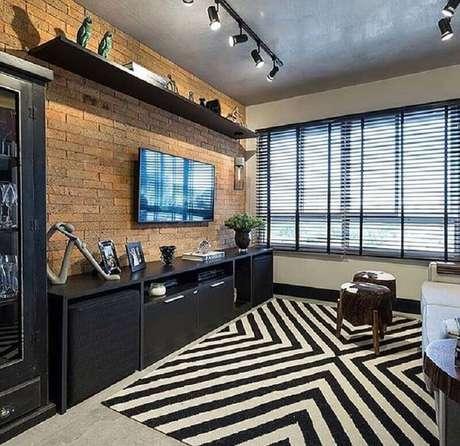 48. Decoração de sala moderna com móveis pretos e TV na parede sem painel – Foto: We Heart It
