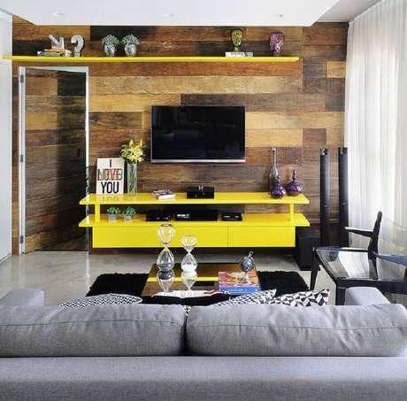 51. Sala simples decorada com rack amarelo e TV na parede com revestimento que imita madeira – Foto: Viajando no Apê