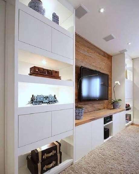 55. Decoração de sala planejada com estante branca e TV na parede com revestimento de madeira – Foto: Pinterest