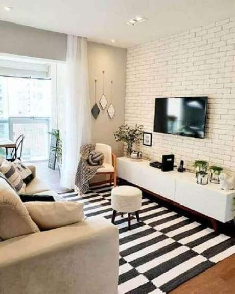 63. Sala branca decorada com tapete listrado preto e branco e TV na parede sem painel – Foto: Pinterest