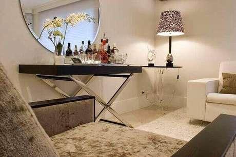 10- O espelho redondo na parede juntamente com o aparador espelhado bar compõe a decoração da sala de estar. Fonte: Pinterest
