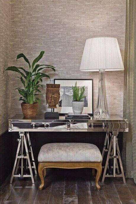 33- Cavaletes cromados servem de suporte para tampo espelhado de aparador. Fonte: Artefacto