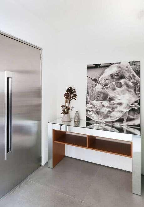 1- O aparador espelhado complementa a decoração onde a porta de entrada é de inox escovado. Fonte: Pinterest