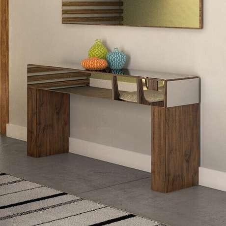 42- O aparador espelhado com pés de madeira tem um visual moderno. Fonte: Pinterest