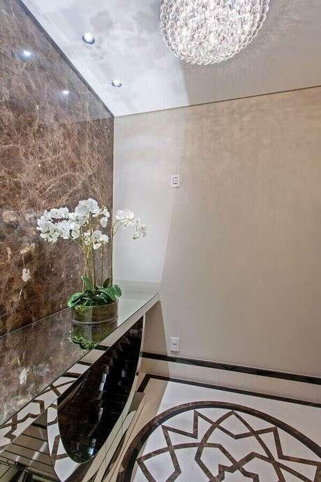 48- Desenho do piso do hall de entrada é valorizado pelo reflexo no aparador espelhado. Fonte: Iara Kilaris