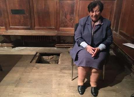 Annie ao lado do alçapão da capela