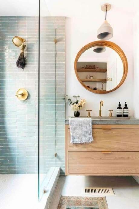 23. Decoração com gabinete suspenso e espelho para banheiro redondo com moldura de madeira – Foto: Apartment Therapy