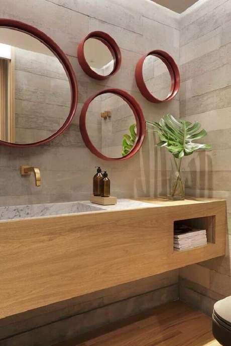 27. Decoração de banheiro moderno com gabinete planejado e vários espelhos para banheiro redondo com moldura vermelha – Foto: Casa de Valentina