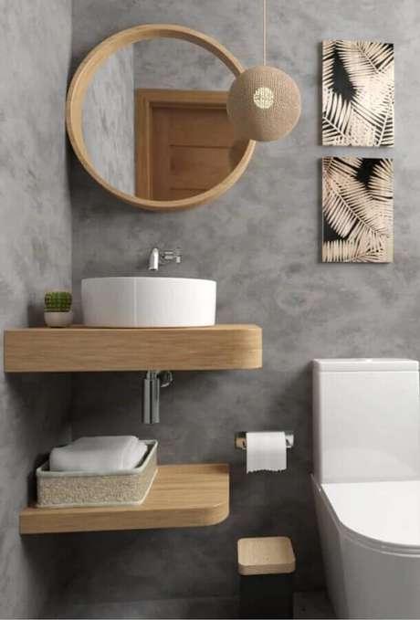 28. Banheiro cinza pequeno decorado com bancada suspensa e espelho redondo para banheiro com moldura de madeira – Foto: Artect Arquitetos