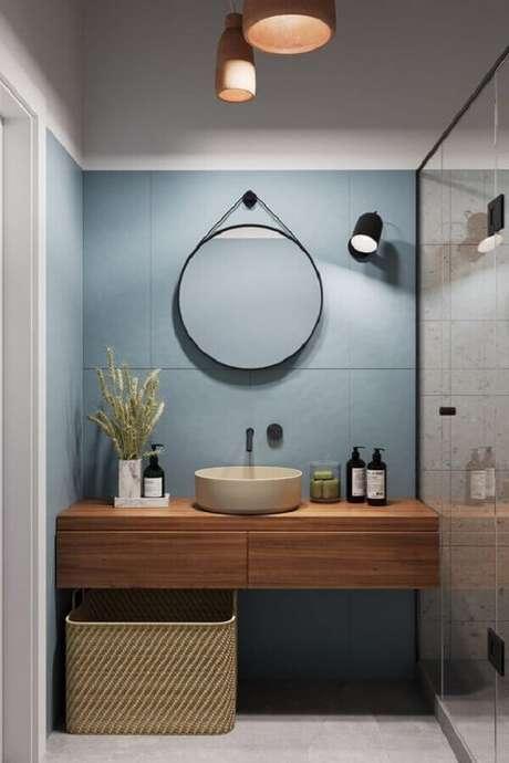 38. Banheiro moderno decorado com parede azul e espelho redondo para banheiro com alça – Foto: Aresto Arquitetura
