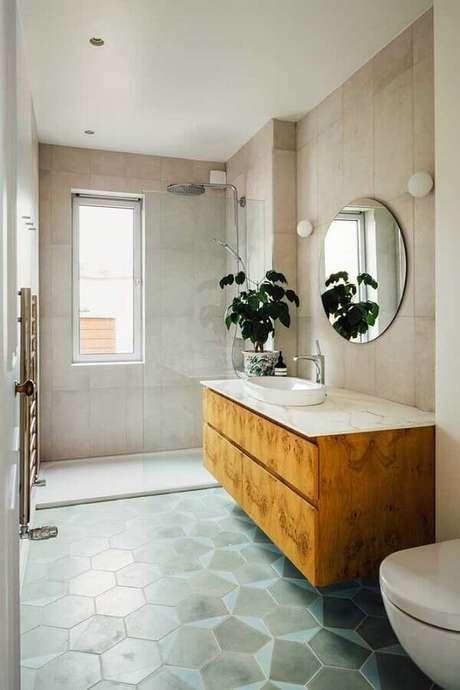 39. Banheiro simples decorado com gabinete de madeira e espelho para banheiro redondo sem moldura – Foto: Pinterest