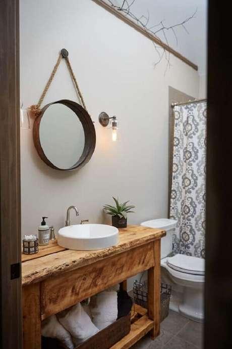 41. Banheiro simples decorado com gabinete rústico e espelho redondo para banheiro com alça de corda – Foto: One Kindesign