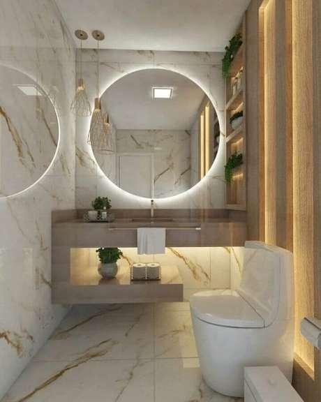 43. Decoração sofisticada com espelho redondo para banheiro com iluminação embutida – Foto: OKA Arquitetura