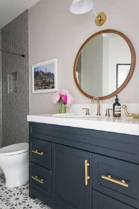 48. Banheiro clássico planejado com gabinete cinza com puxadores dourados e espelho redondo para banheiro com moldura de madeira – Foto: HGTV
