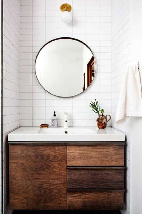 51. Espelho redondo para banheiro com gabinete de madeira rústica – Foto: Apartment Therapy
