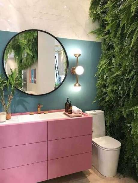 52. Espelho redondo para banheiro decorado com jardim vertical e gabinete rosa – Foto: We Heart It