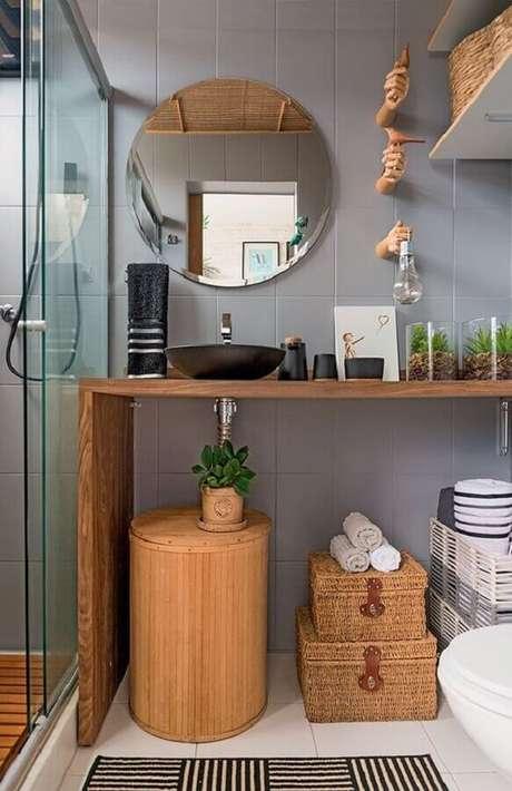 55. Espelho redondo para banheiro simples decorado com bancada de madeira – Foto: Pinterest