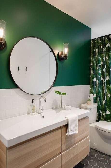 56. Espelho redondo para banheiro decorado com arandela de vidro e parede verde – Foto: Decoist
