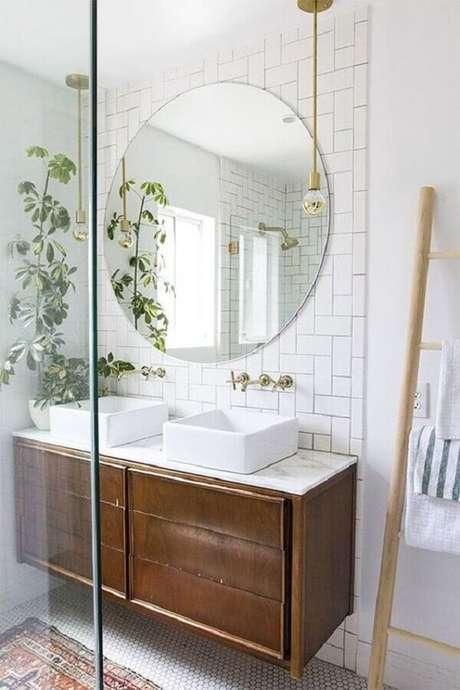 57. Decoração clean com espelho redondo para banheiro com gabinete suspenso de madeira – Foto: PURE Design Inc.