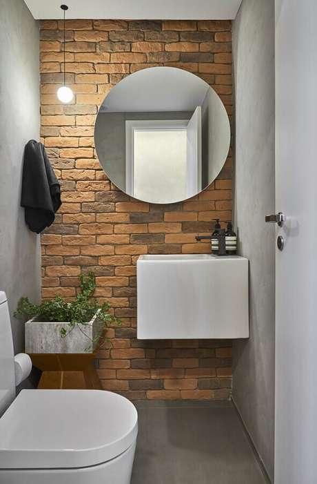 62. Espelho redondo para banheiro pequeno decorado com parede de tijolinho à vista – Foto: Conexão Décor