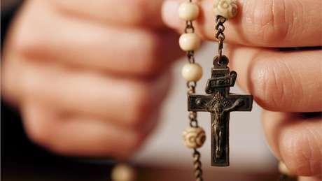 Mão segurando crucifixo