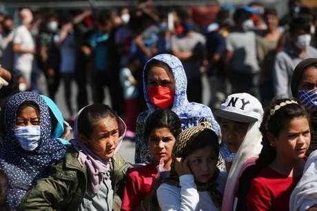 Refugiados esperam por comida em acampamento incendiado em Lesbos, na Grécia