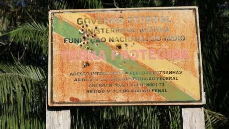 Esta placa crivada de balas na fronteira de uma reserva indígena no Brasil é uma evidência do aumento das tensões