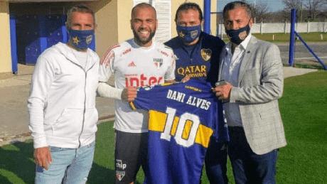 Daniel Alves recebeu a camisa da equipe de Buenos Aires das mãos de executivos do clube (Foto: Reprodução)
