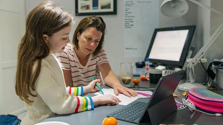 """Mulher ajudando filha na escola, em foto de arquivo; """"entre a população que trabalha de casa, as mulheres passam significativamente mais tempo (ocupando-se) da educação e dos cuidados das crianças"""", diz estudo de Cambridge"""