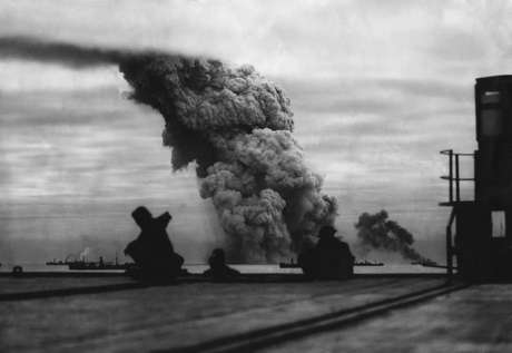 KWB6RM Smoke from a merchant ship bombed in an Allied convoy to the Soviet Union (Russia). The convoy fought through a four-day attack by German torpedo planes and U-boats to deliver cargo to a Soviet Arctic port. October 1942 during World War 2. (BSLOC_2014_8_34)