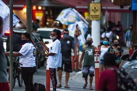 Campanha política toma cruzamento no Perequê em Ilhabela, SP, no fim desta tarde de terça-feira. Cabos eleitorais agitam bandeiras e distribuem santinhos aos transeuntes e motoristas.