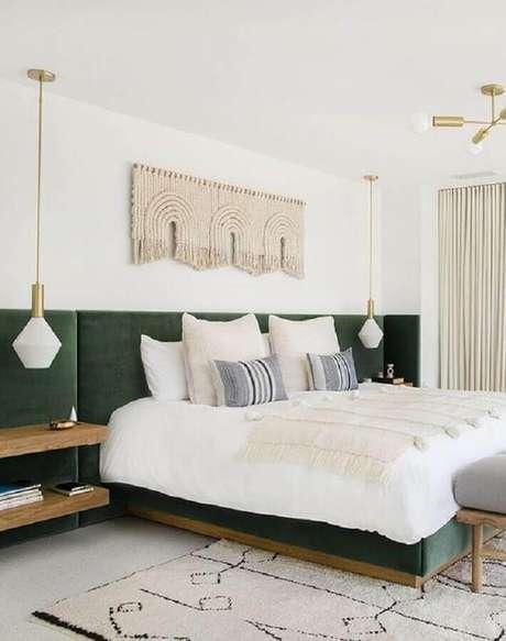 13. Quarto de casal amplo decorado com cabeceira estofada verde e luminária pendente de cabeceira – Foto: Apartment Therapy
