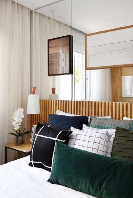 15. Quarto decorado com várias almofadas, parede espelhada e luminária pendente de cabeceira – Foto: Dicas de Mulher