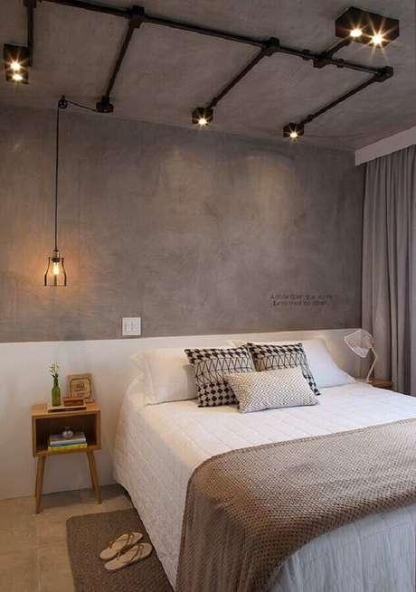 17. Decoração industrial para quarto com parede de cimento queimado e luminária pendente de cabeceira – Foto: Casa de Valentina