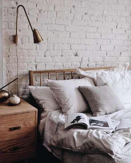 22. Quarto rústico decorado com parede de tijolinho branca e luminária de cabeceira para leitura em ouro envelhecido – Foto: Parachute