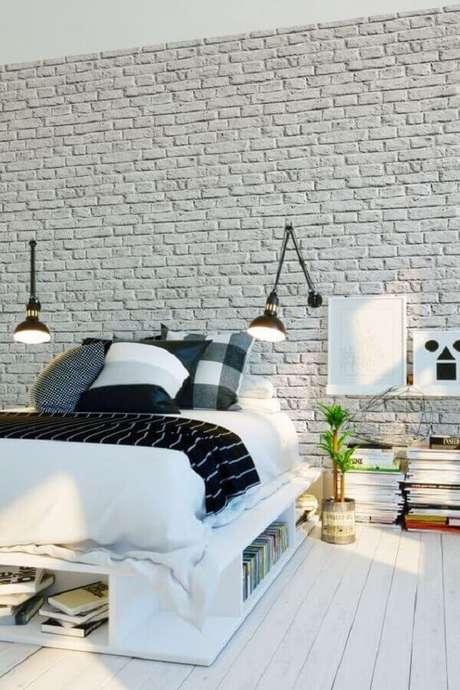 26. Luminária de cabeceira para leitura em quarto de casal decorado com várias almofadas e parede de tijolinho branca – Foto: Parachute