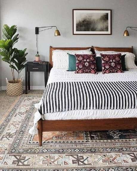 27. Decoração de quarto de casam com cama de madeira e luminária de cabeceira de parede – Foto: Ariyona Interior