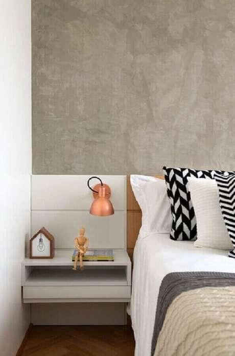 31. Quarto de decorado com luminária de cabeceira rose gold e parede de cimento queimado – Foto: Jeito de Casa