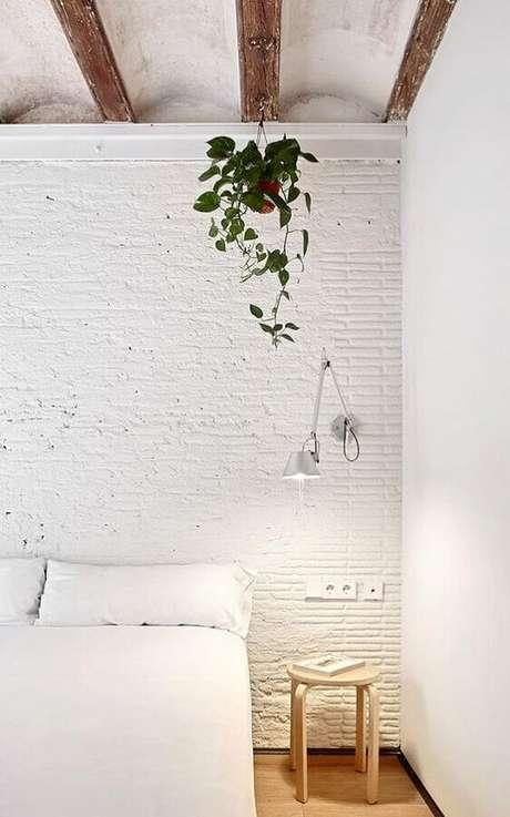 46. Quarto branco com parede de tijolinho rústica decorado com luminária de cabeceira articulada para leitura – Foto: HomeWorldDesign