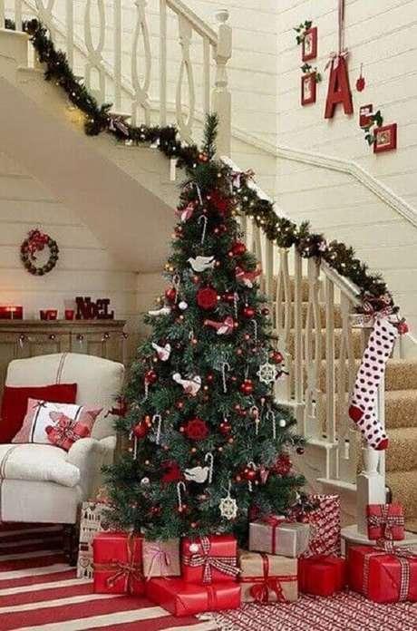 19. Sala decorada com árvore natalina e festão de Natal verde para escada – Foto: Elle Decor